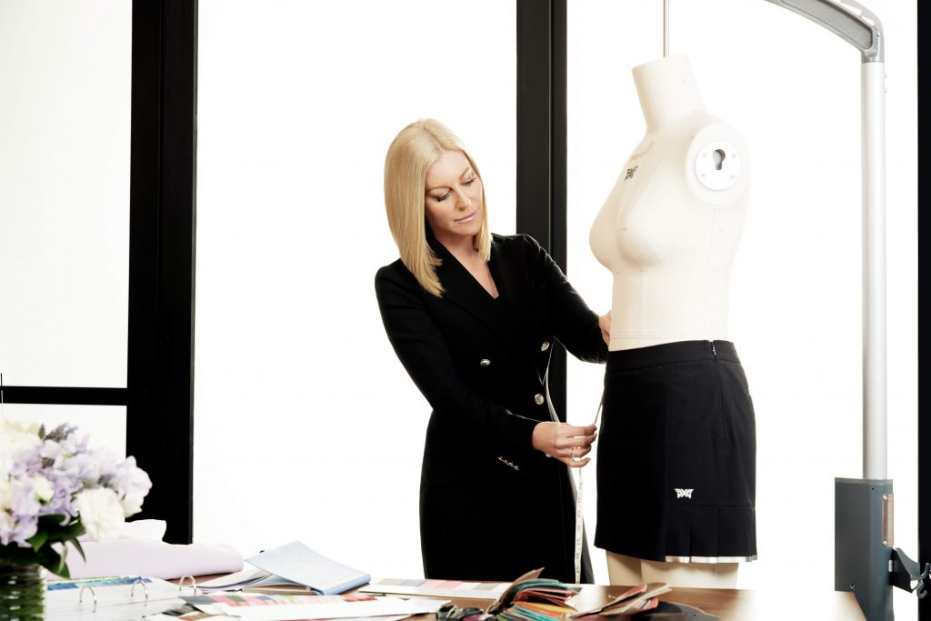 Renee Parsons in her office measuring a garment